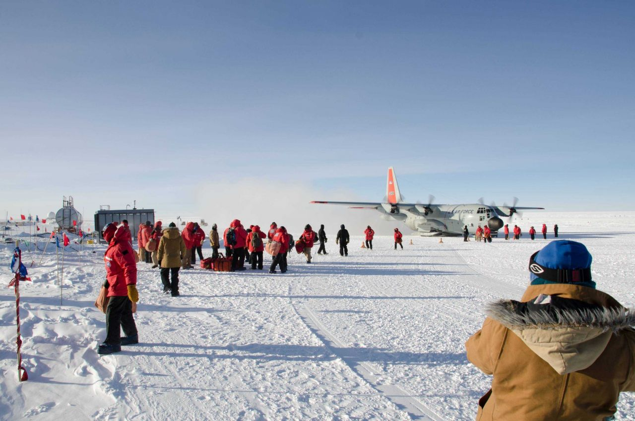 Scientists arriving at South Pole Station and disembarking from C-130 aircraft. Photo