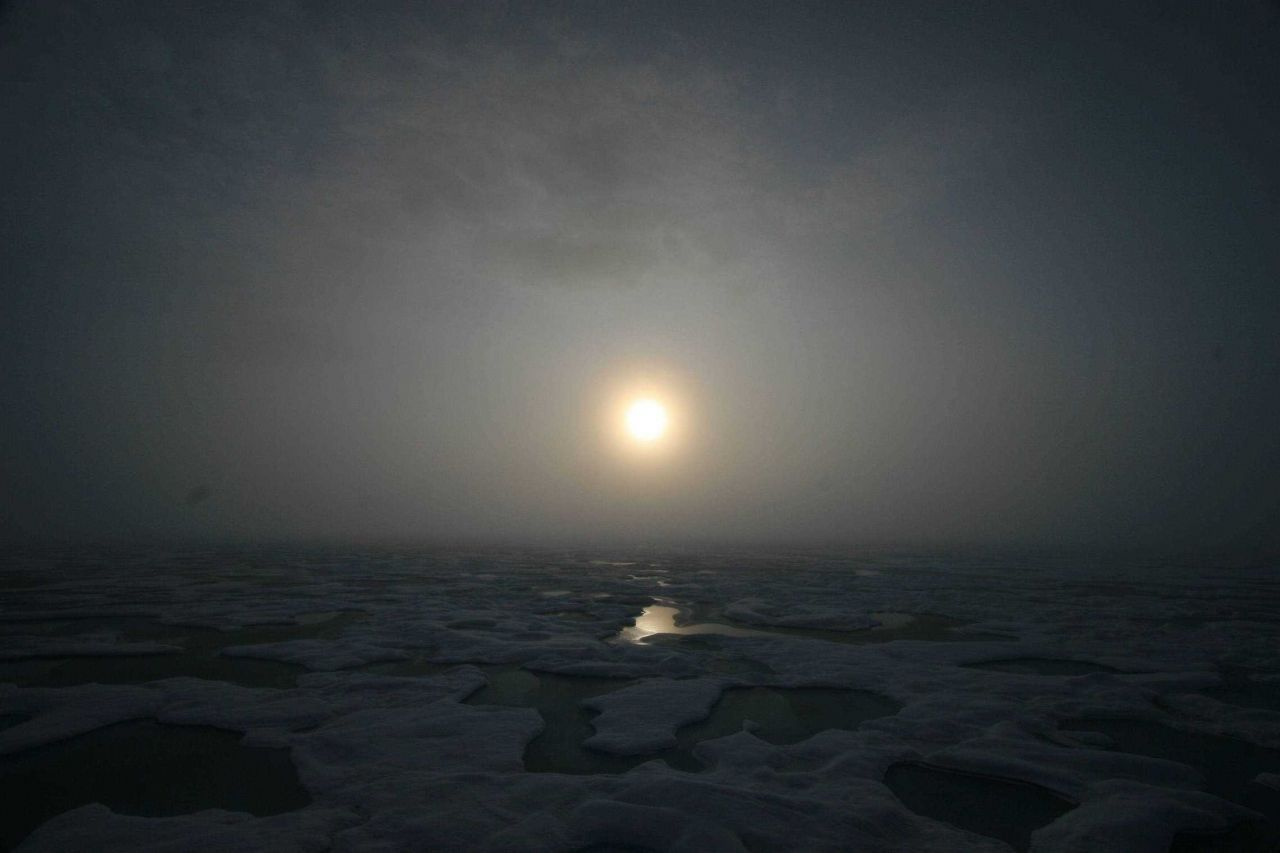 Sun seen through the clouds over melt pools and hummocky ice on a gloomy day. Photo