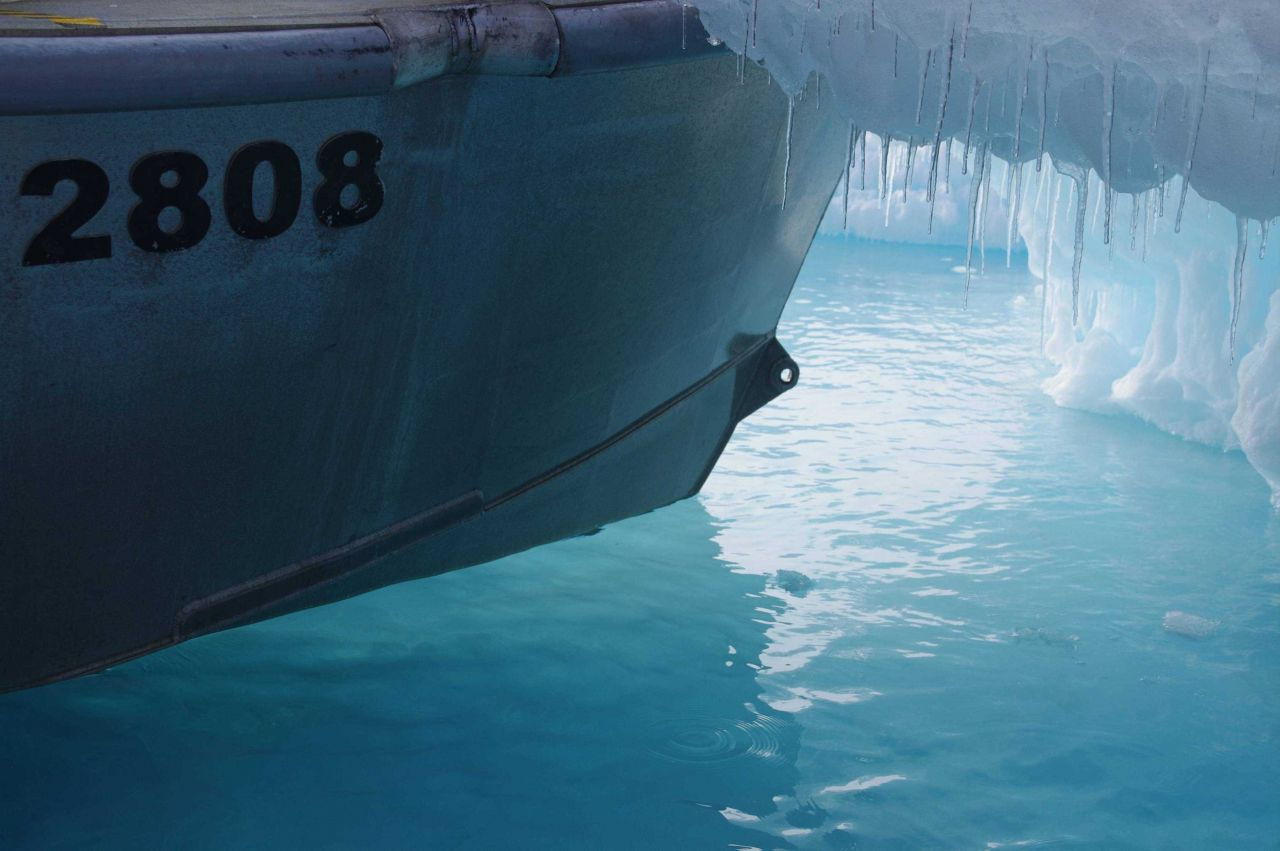 Bow of survey launch from NOAA Ship FAIRWEATHER in tied up to small iceberg. Photo