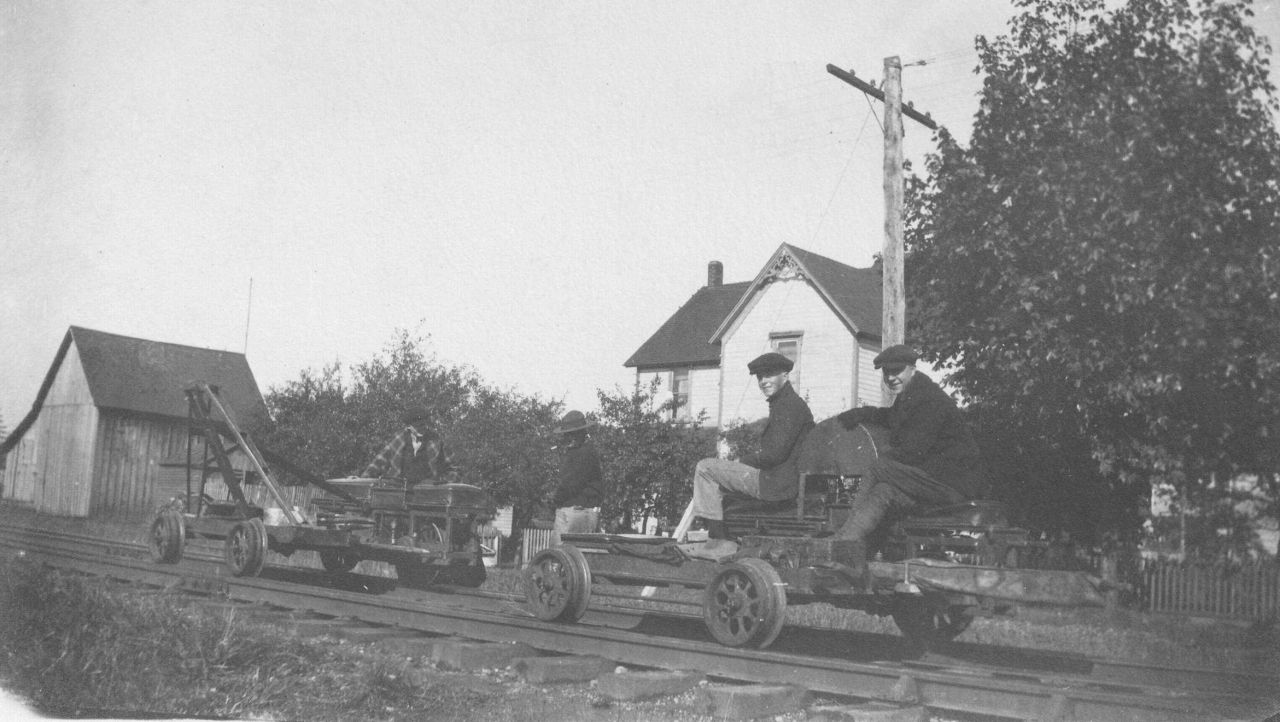 Level crew using motorized speeders on railroad. Photo