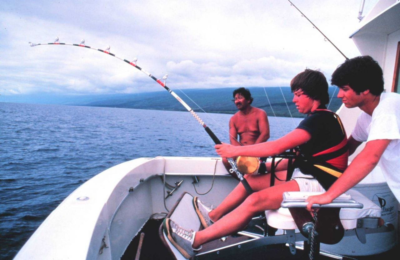 Charter vessel (CPFV) angler in fighting chair, hooked on a big marlin Photo