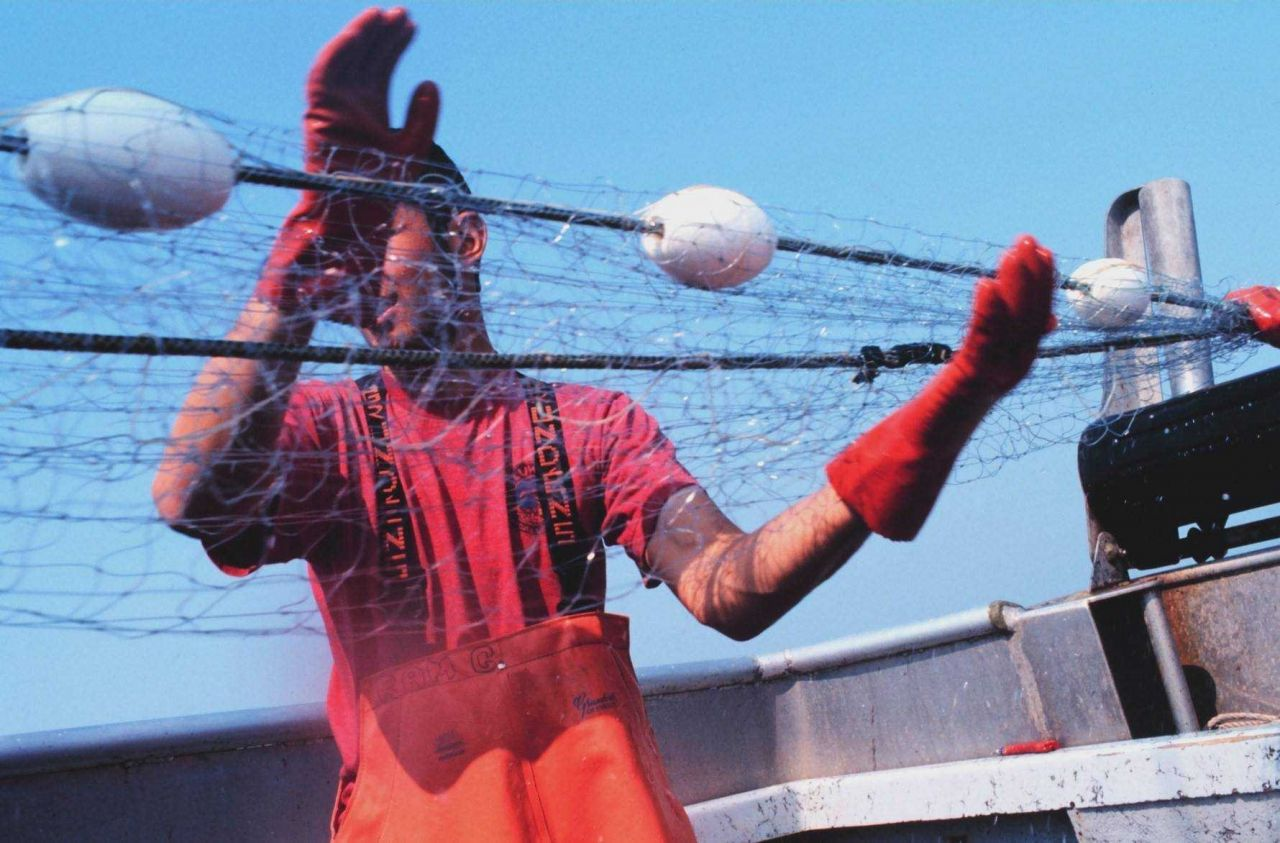 Rama Geroux, a crew member of a salmon fishing vessel, monitoring gillnet as it is reeled in Photo
