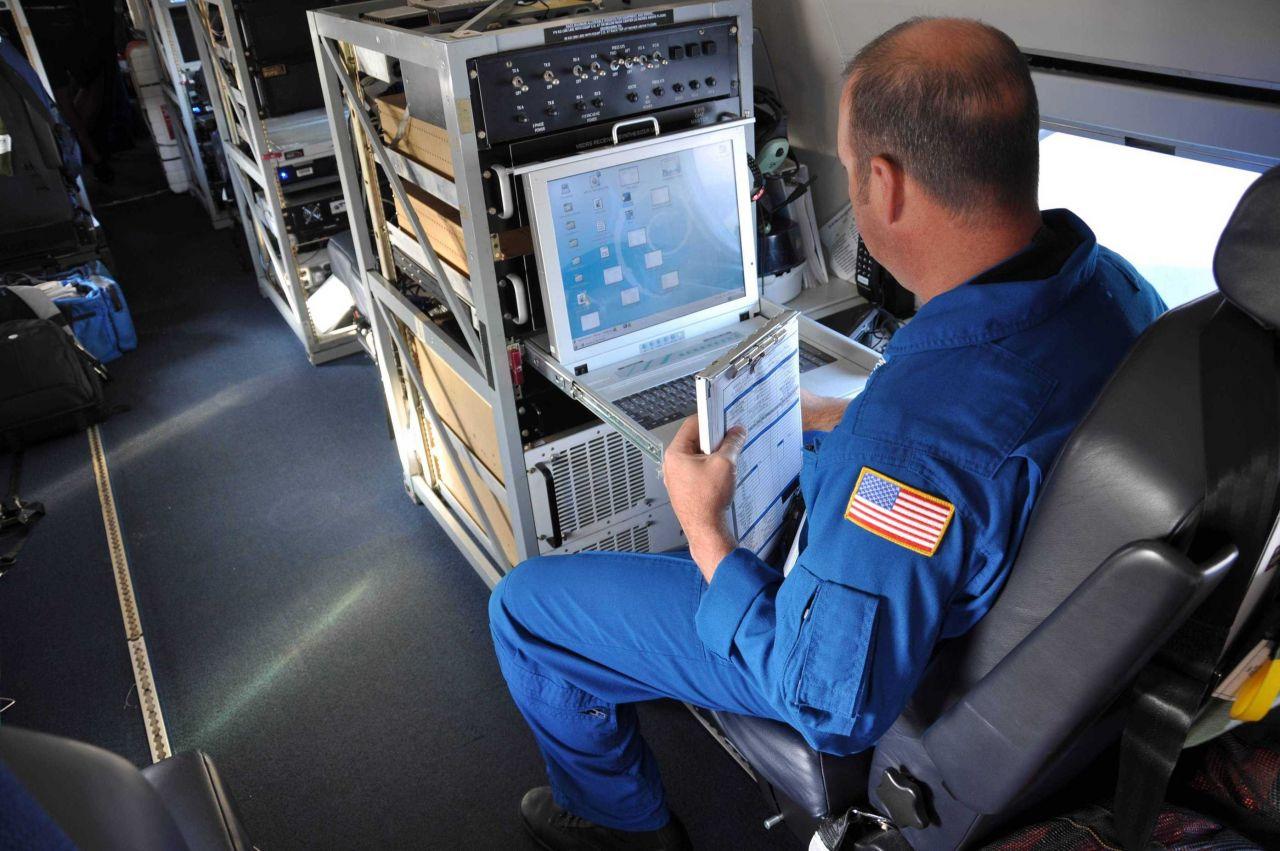 Lead Electronics Technician Gabriel Defeo aboard NOAA Gulfstream IV jet during February 2013 mission out of Honolulu_ Photo