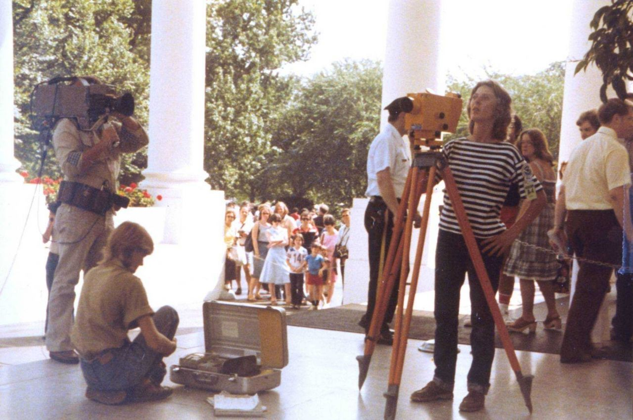 Anita Whitis being filmed by news crew while conducting leveling operations on the North Portico of the White House. Photo