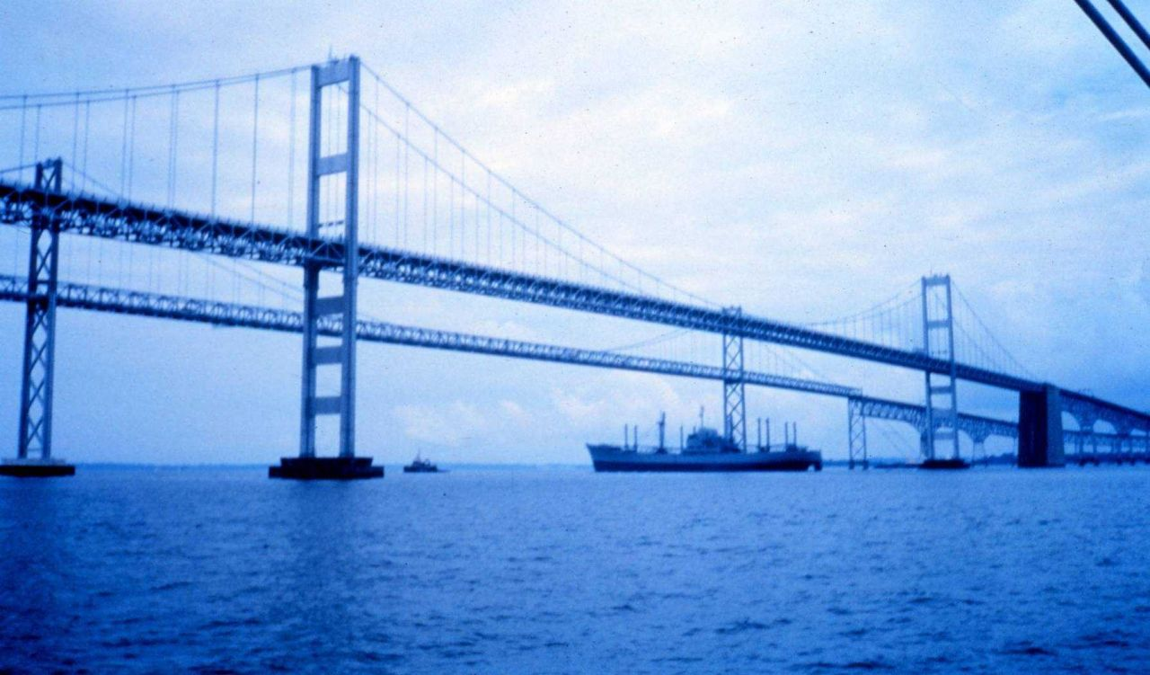 A tugboat tows an old freighter down the bay and under the Chesapeake Bay Bridge . Photo