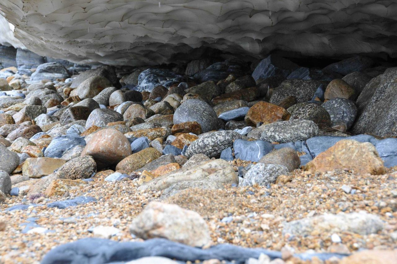 Below the melting ice surface lie rounded boulders, attesting to the violence of Bering Sea surf near Tin City and Cape Prince of Wales. Photo