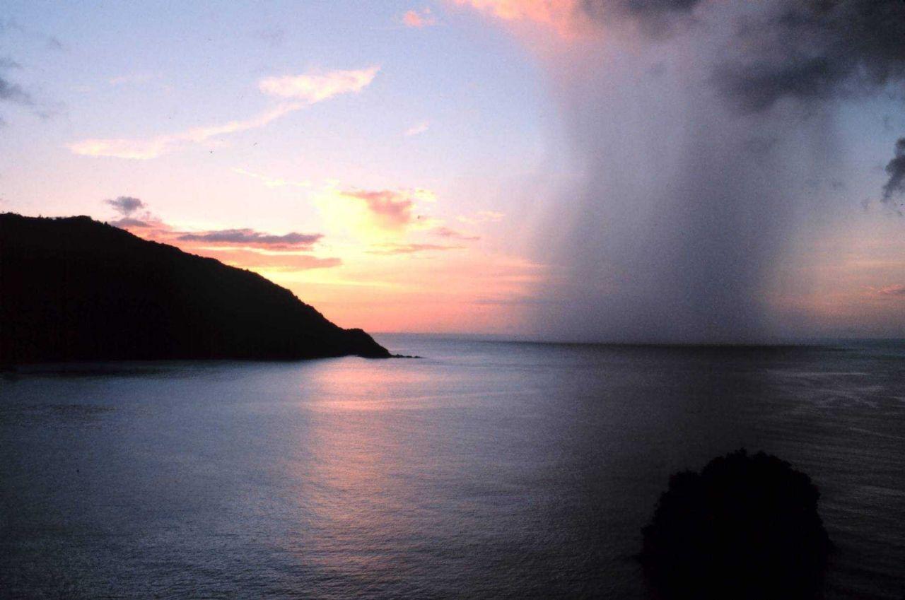 A rain shaft pierces a tropical sunset as seen from Man-of-War Bay. Photo