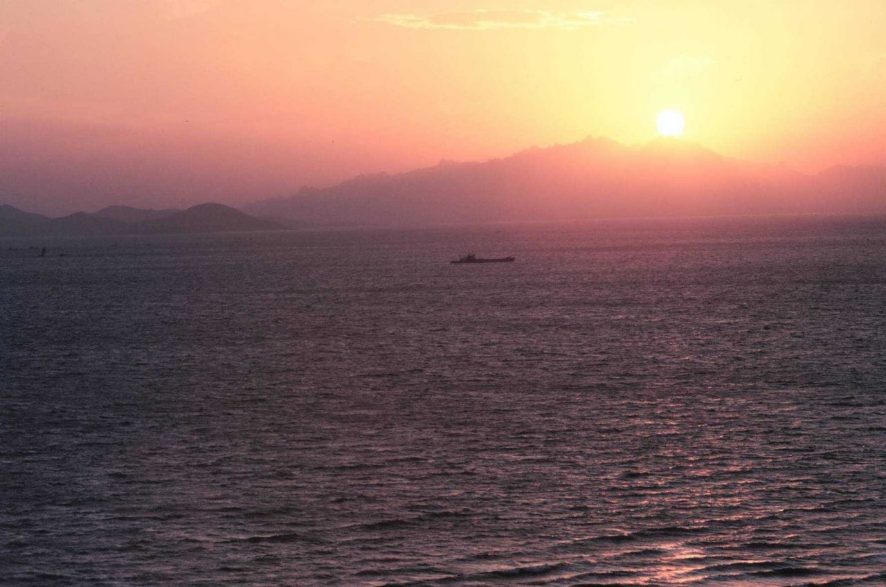 Sunset over mountains and ocean Photo