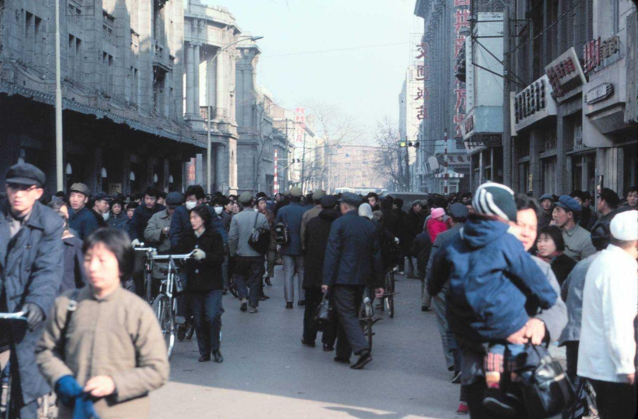 Citizens crowding an urban street: bikes, pedestrians, but no cars. Photo