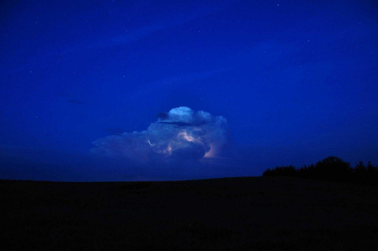 Supercell thunderstorm illuminated by lightning at night Photo