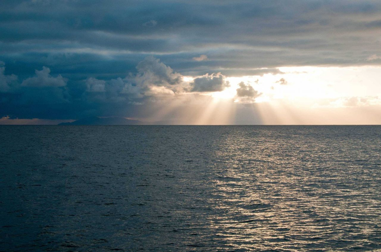 Crepuscular rays streaming through the clouds in the Channel Islands. Photo