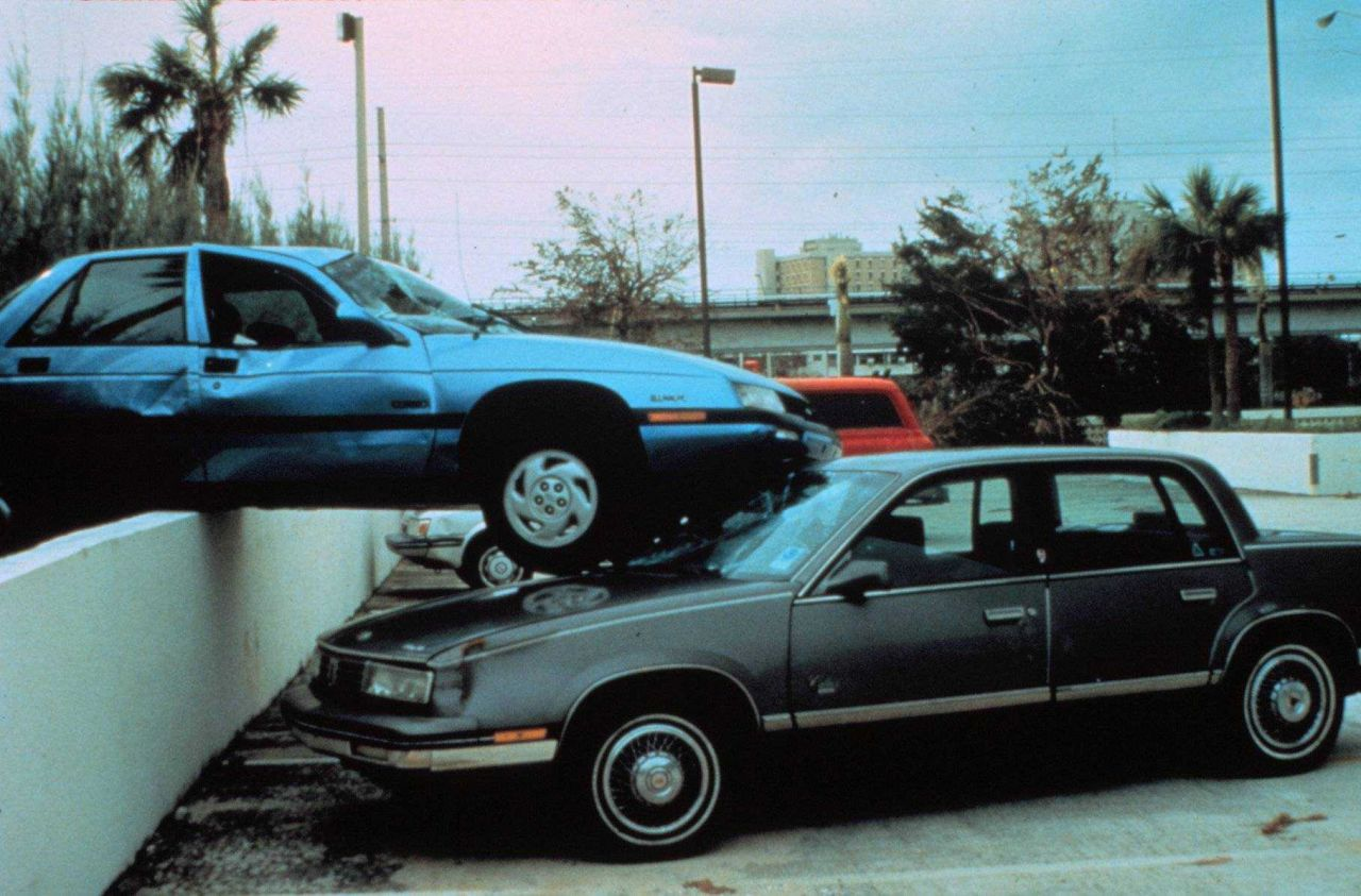 Hurricane Andrew - Vehicle picked and deposited on wall and other vehicle Vehicles belonged to CNN reporter and Hurricane Center employee Hurricane Ce Photo