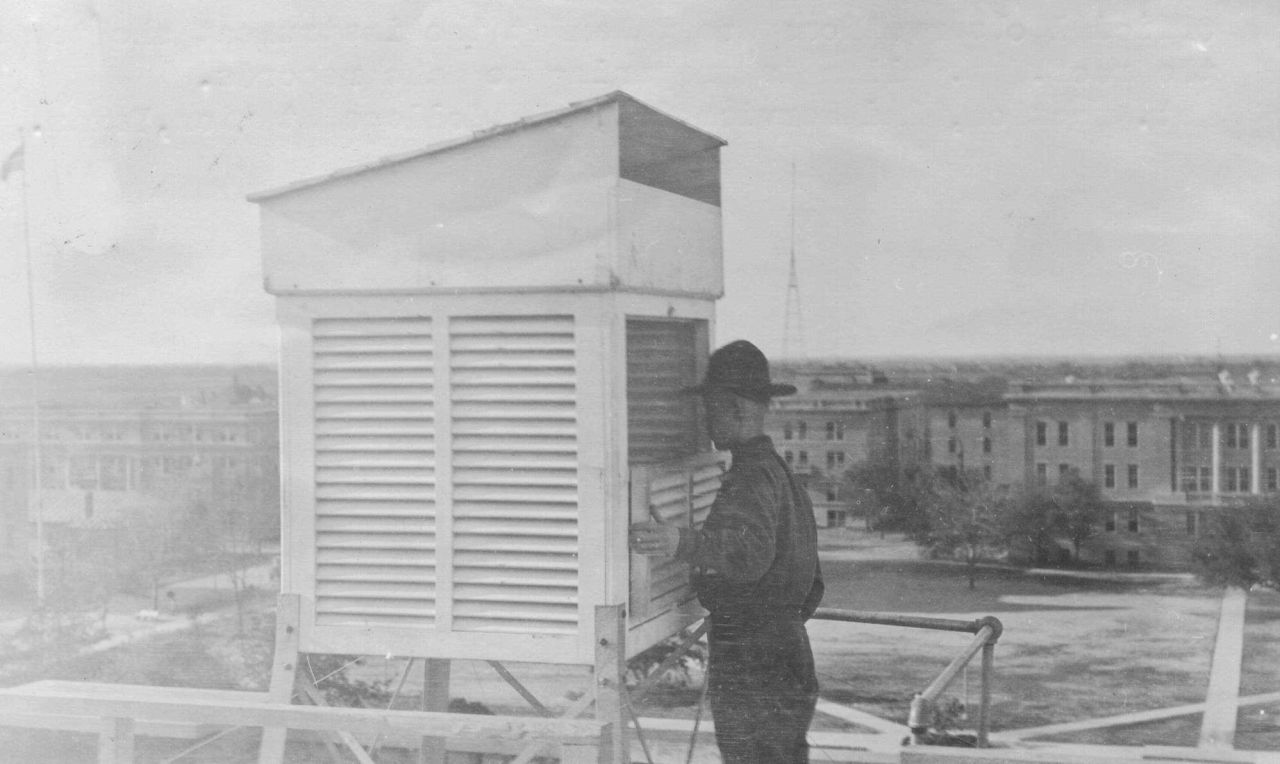Signal Corps meteorological student Callen opening an instrument shelter in order to read thermometers. Photo