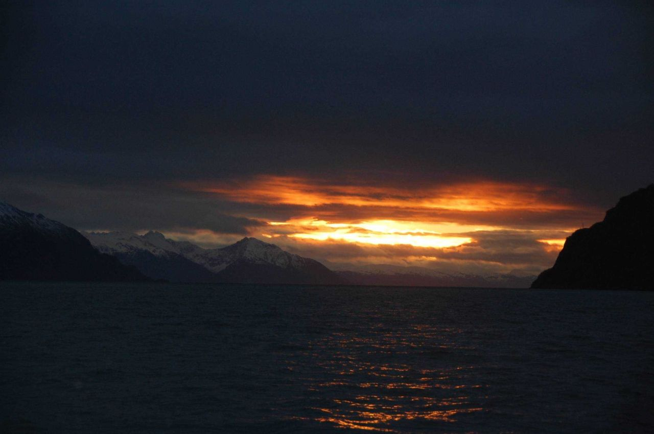 Dramatic sunset over ocean and mountains. Photo