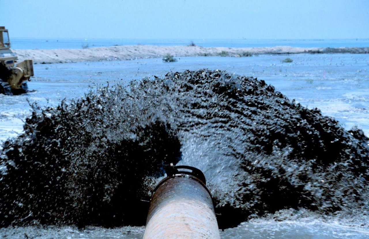 An extreme close up view of sediment being pumped onto the marsh platform. Photo