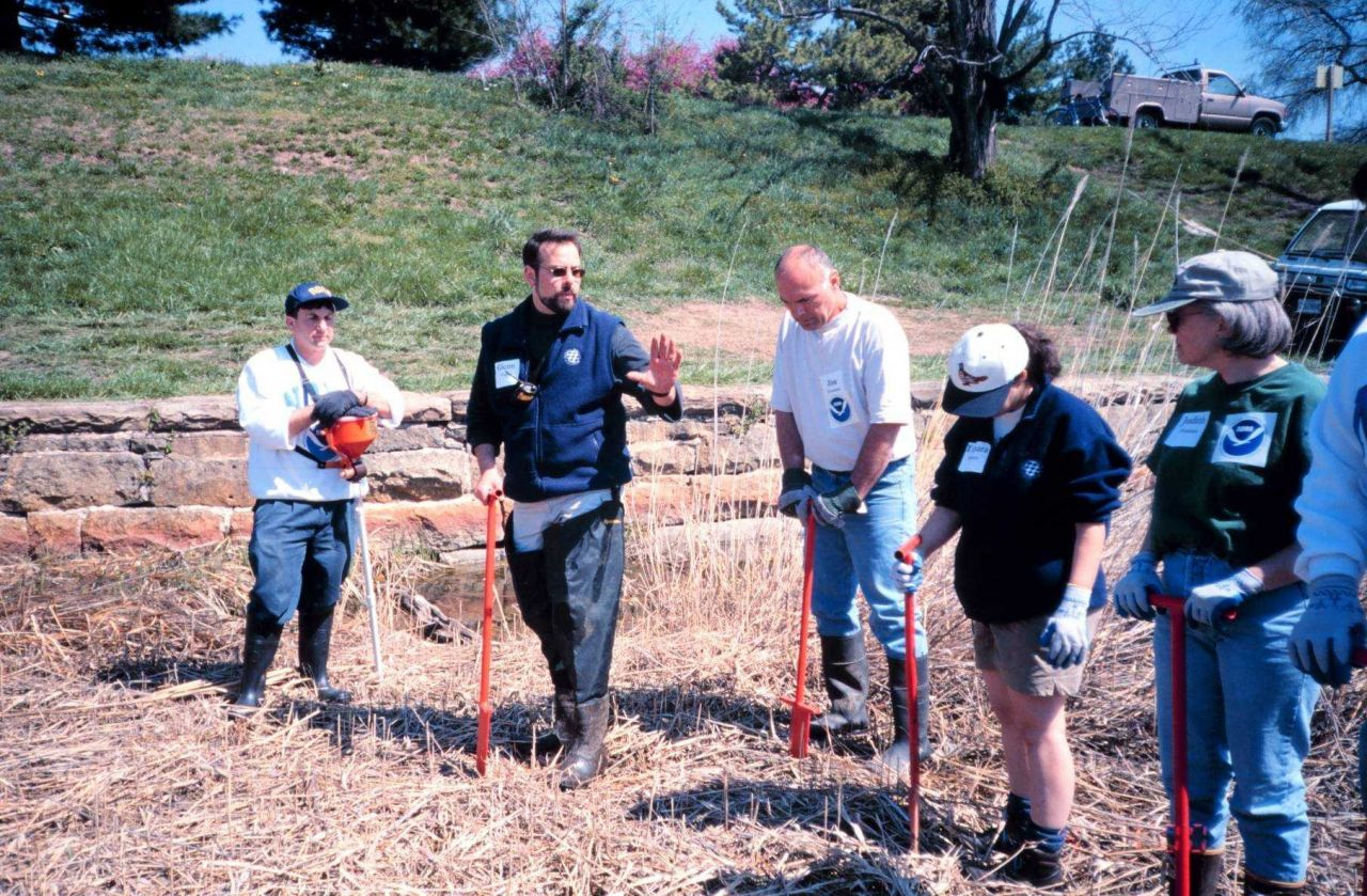 Glenn Page, the Conservation Director for the National Aquarium in Baltimore, instructs volunteers in planting techniques and in using a dibble. Photo