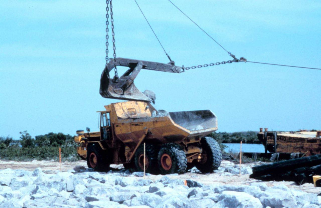 A crane loads rock from the barge into a truck. Photo