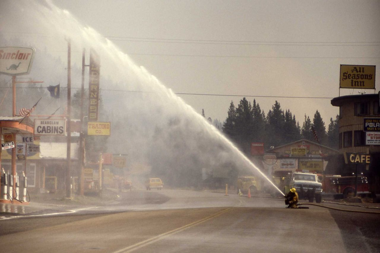 Firefighters spraying water over business district in Cooke City, Montana Photo