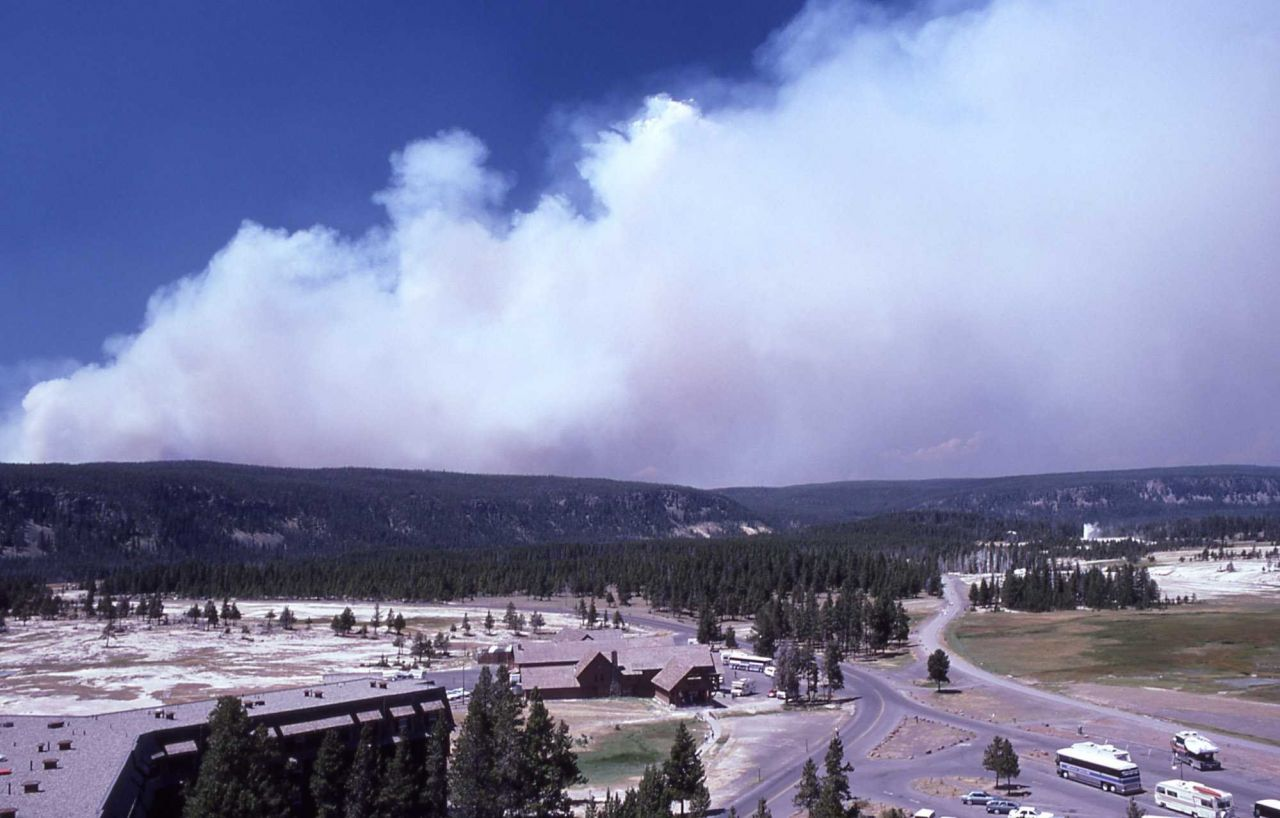 Dense smoke rising from Madison Plateau with geyser erupting in distance - taken from crow's nest at Old Faithful Inn Photo