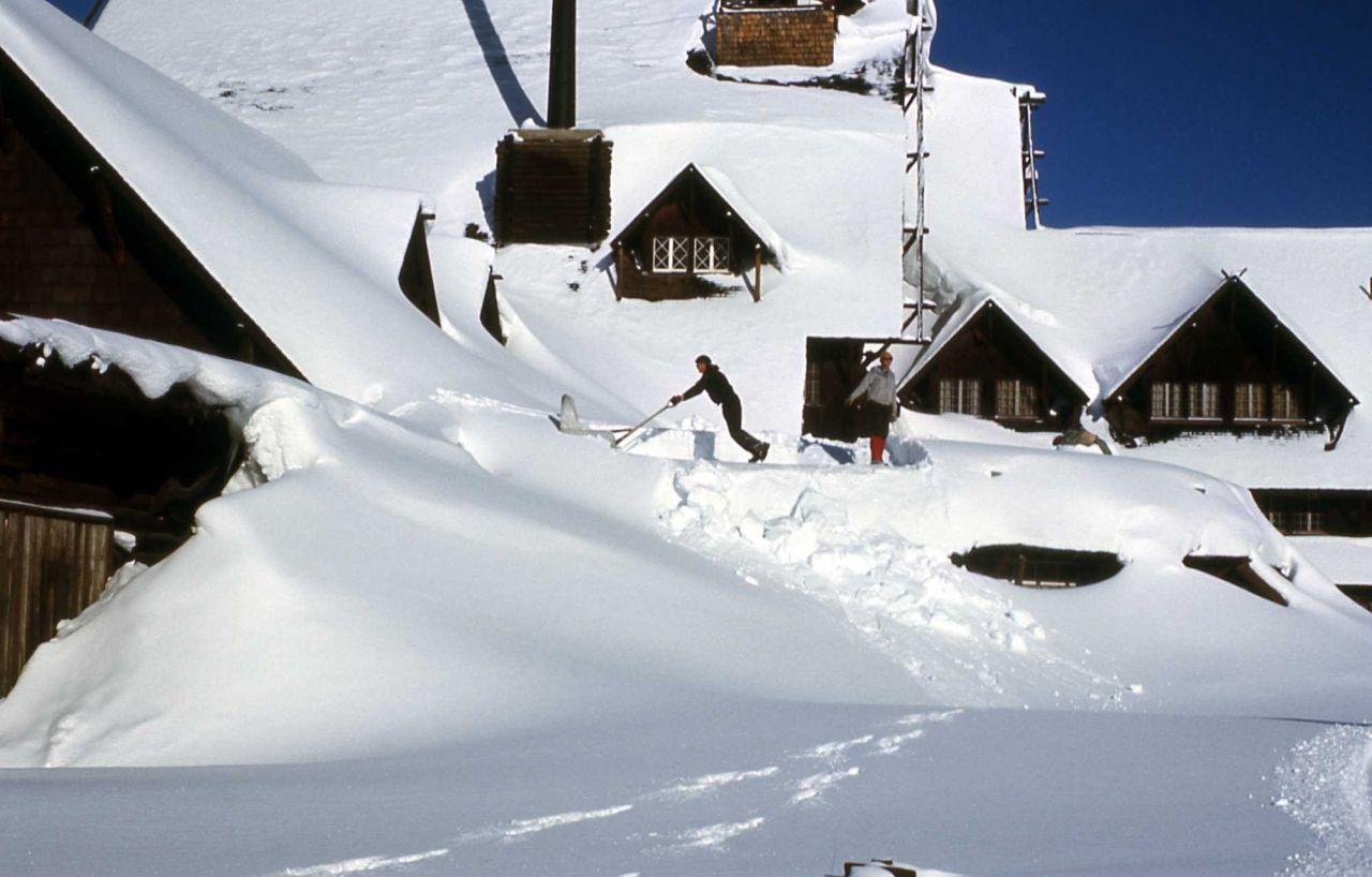 Maintenance worker shoveling snow off of Old Faithful Inn Photo