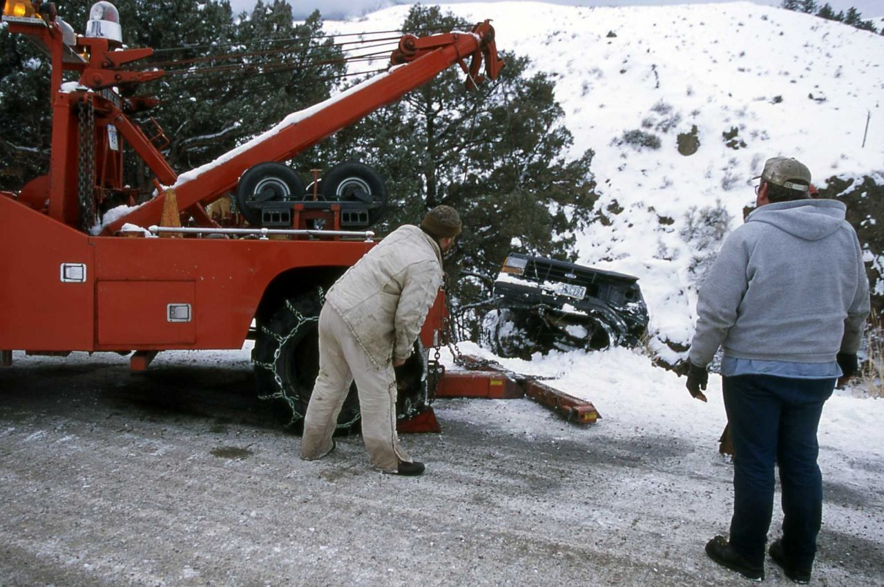 YPSS (Yellowstone Park Service Stations) tow truck pulling a pickup out of the Gardner River Photo