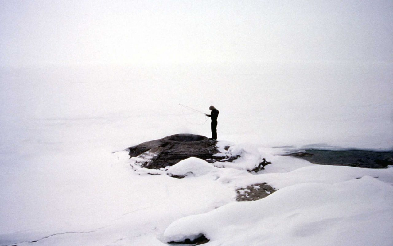 Interpretive Ranger Roger Anderson taking winter temperature in fishing cone at West Thumb Geyser Basin Photo