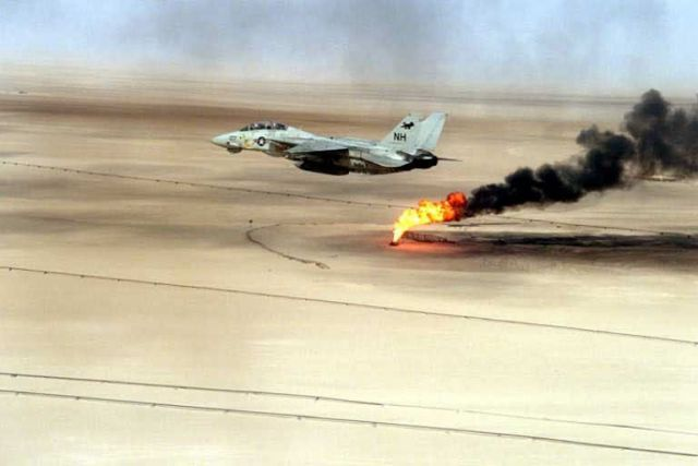 Navy F-14 - A Navy F-14 Tomcat flying over a burning oil field in Kuwait Picture