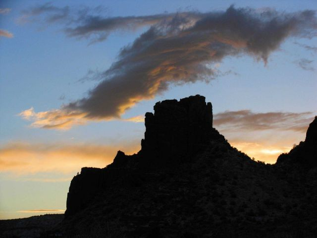 A castle-like rock structure silhouetted in the sunset Picture