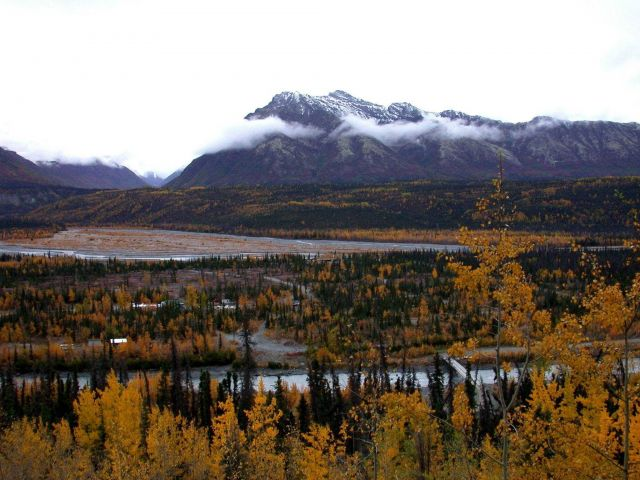 Fall foliage, a river bridge below and a highway leading into a seemingly endless wilderness. Picture