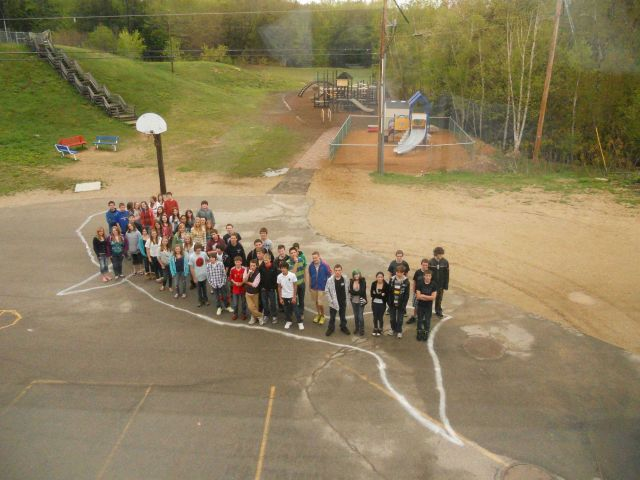 Students filling outline of Northern right whale drawn on the playground of Deefield Community School. Picture