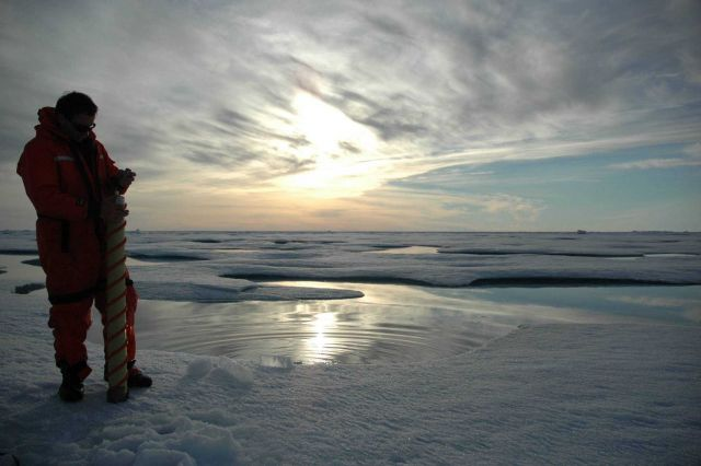 Rolf Gradinger is silhouetted by the Arctic sun while collecting an ice core. Picture