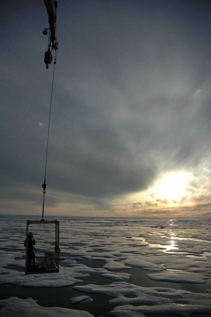 Transportation off the ship as a scientist is being transported to the ice surface from the USCG Icebreaker HEALY under the midnight sun. Picture