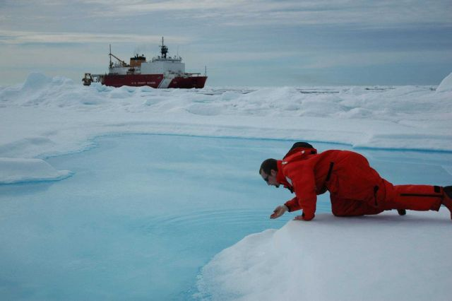 Scientist testing the waters so to speak with the USCG Icebreaker HEALY in the background. Picture