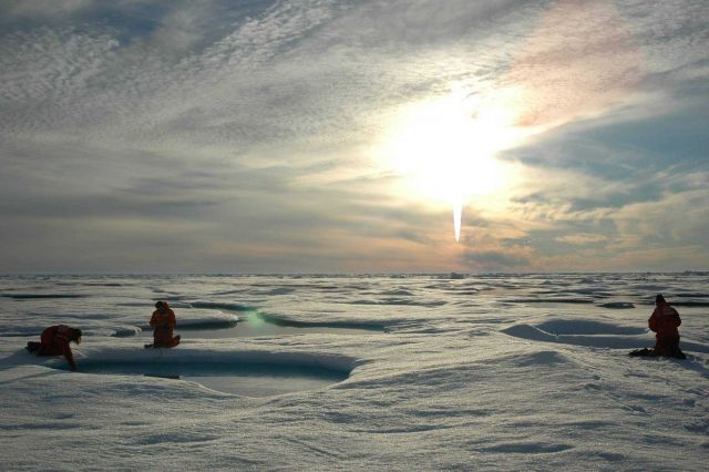 Scientists working on the ice beneath the midnight sun. Picture