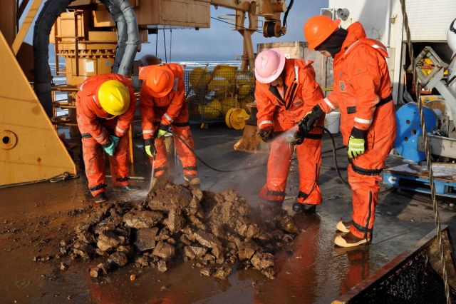 Scientists inspecting dredge haul of rocks and mud looking for benthic life forms. Picture