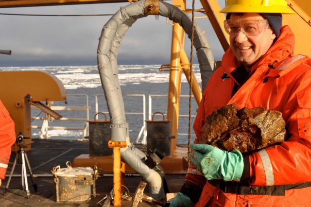 Scientist with rock hammer and specimen of rock from bottom of Beaufort Sea. Picture
