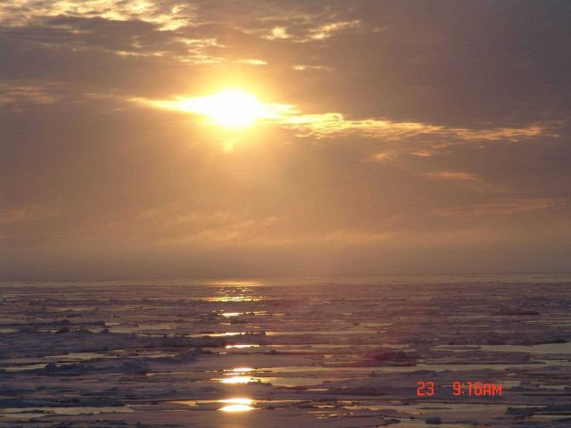 An amber sun reflecting off ice floes, melt pools and a polynya in the distance. Picture