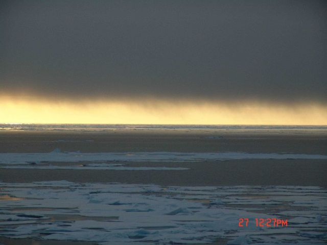 A dark blanket of cloud framing a yellow-gold sun illuminated horizon with ice floes and a polynya below. Picture