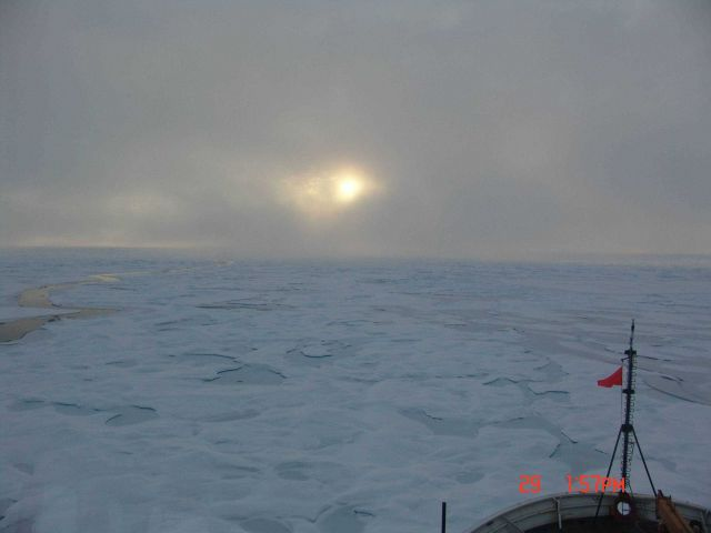 Sun peaking through the clouds while the HEALY plows through ice floes and melt ponds Picture