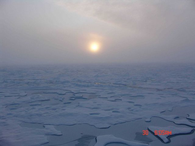 Sun seen through the clouds seen over ice floes and melt ponds. Picture