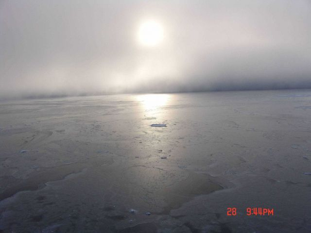Sun seen through the clouds reflecting off grey ice. Picture