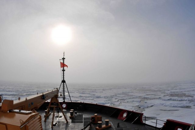 Sun seen through the clouds over the jackstaff as the CGC HEALY proceeds through ice floes. Picture