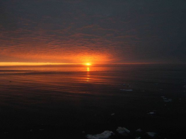 Sun, red sky, and an expanse of open water with small bits of brash ice in foreground. Picture