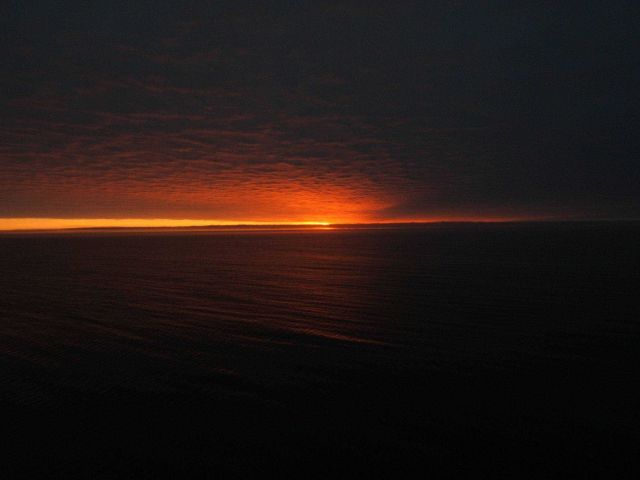 Sun, red sky, and an expanse of open water. Picture
