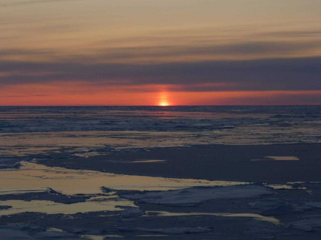 A sun pillar as sun dips below the horizon with ice floes and new ice. Picture