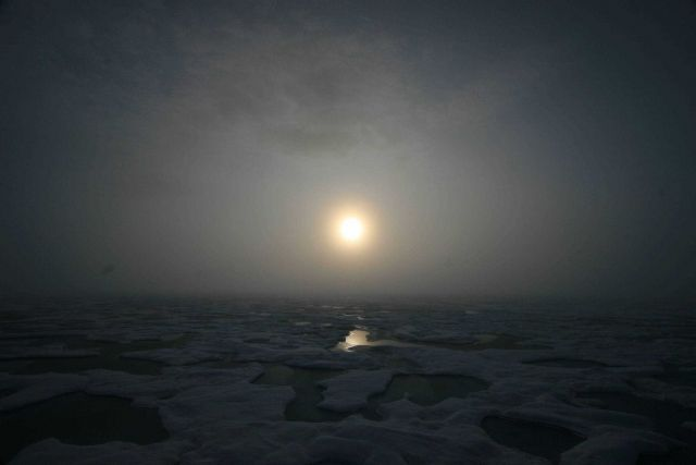 Sun seen through the clouds over melt pools and hummocky ice on a gloomy day. Picture