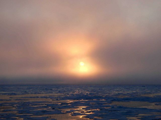 Sun seen through the clouds over late summer ice floes. Picture