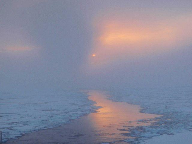 A glimpse of sun illuminating a lead through ice floes Picture