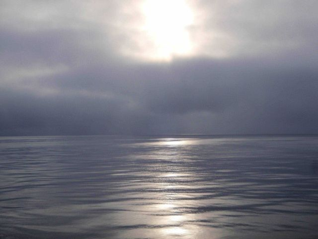 Sun seen through the clouds reflecting on grease ice Picture