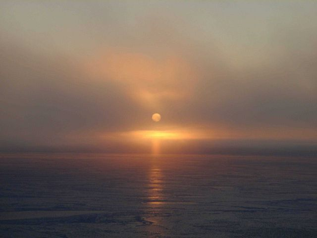 Lower sun pillar seen extending downward from sun and reflecting on new ice. Picture